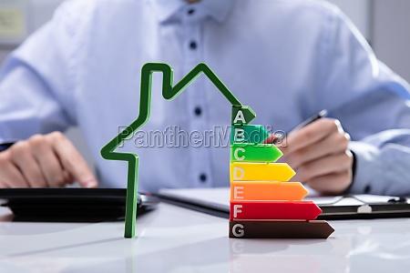 haus mit energieeffizienzrate vor geschaeftsleuten die