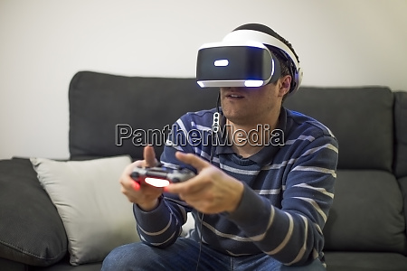 young man wearing vr glasses sitting
