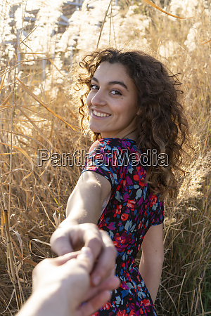 young woman standing in meadow holding