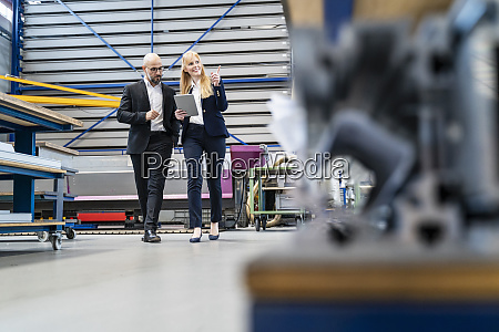 businessman and businesswoman with tablet walking