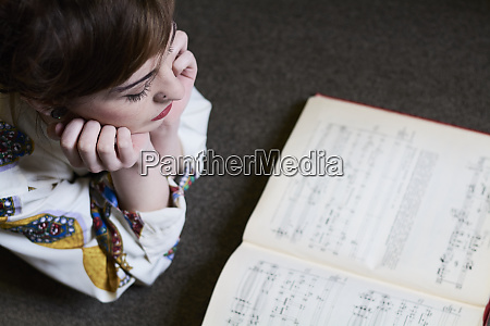 female student reading a music book