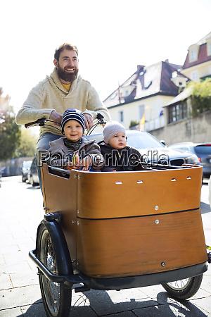 gluecklicher vater mit zwei kindern die
