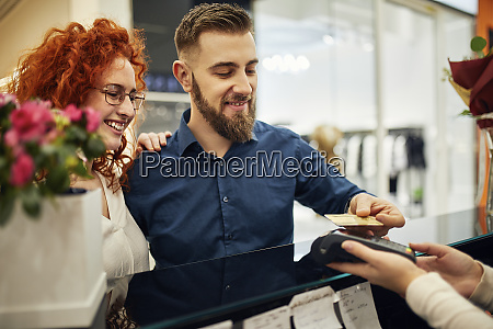 happy couple paying at counter in