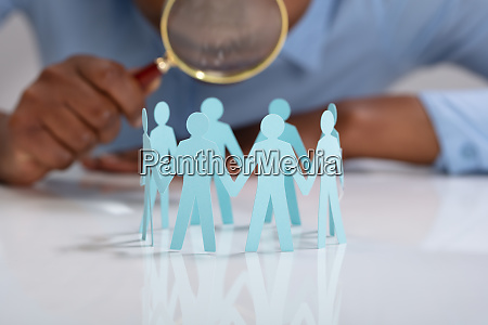 businessperson looking human figures with magnifying