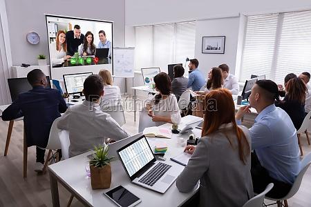 geschaeftsleute nehmen an videokonferenzbesprechung im buero