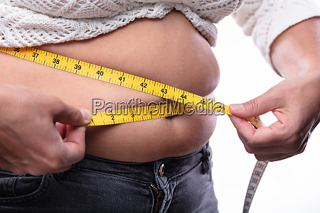 woman measuring her waistline