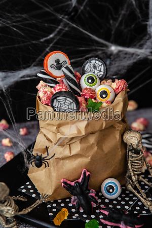 papiertuete voller bunter suessigkeiten fuer halloween