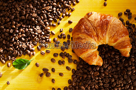 fresh flaky croissant on roasted coffee
