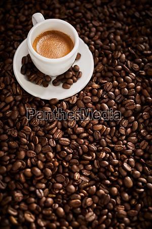 vollgeroestete kaffeebohnentextur mit tasse kaffee