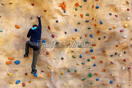 bouldern mann klettert auf kuenstliche