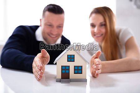 male and female hands protecting house