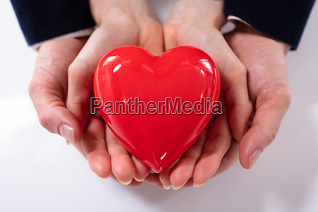 couples hand holding red heart