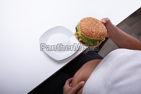 overweight woman holding hamburger in hand