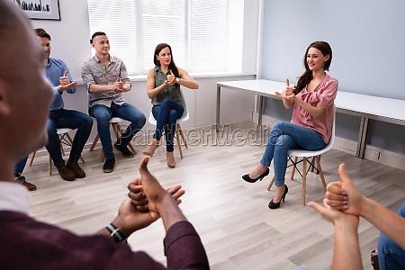 woman teaching deaf gesture sign to