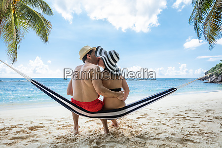 young couple sitting on hammock kissing