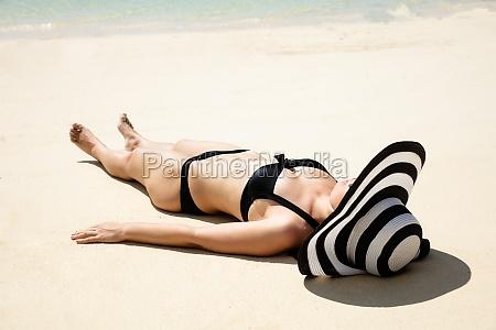 young woman lying on beach near