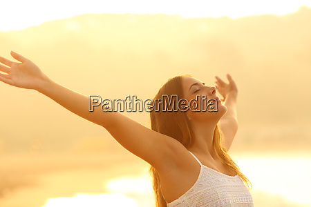 relaxed woman stretching arms breathing fresh