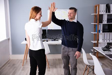 geschaeftsleute geben high five am arbeitsplatz