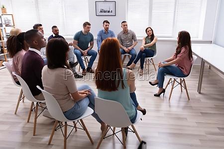 weibliche therapeutin spricht mit gruppe in