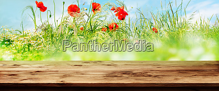 wooden table with flower meadow background