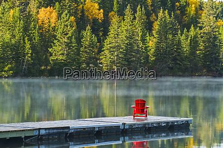 muskoka chair on dock with autumn