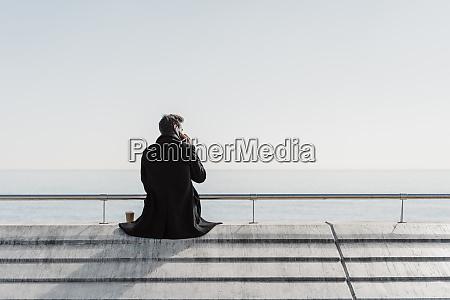 businessman sitting on quay wall talking