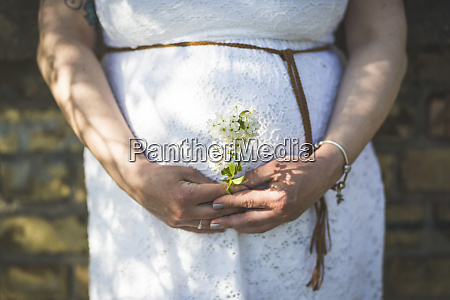 pregnant woman holding flowers close up