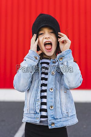 portrait of screaming little girl wearing