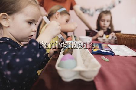 maedchen malen ostereier auf dem tisch