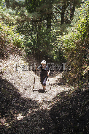 senior woman hiking through forest at