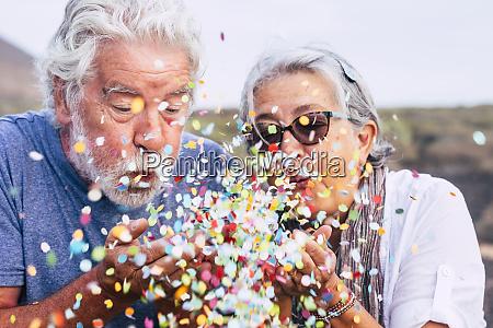 senior paar blaest konfetti im freien