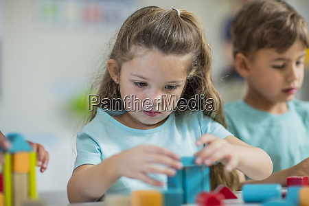 focused girl playing with building blocks
