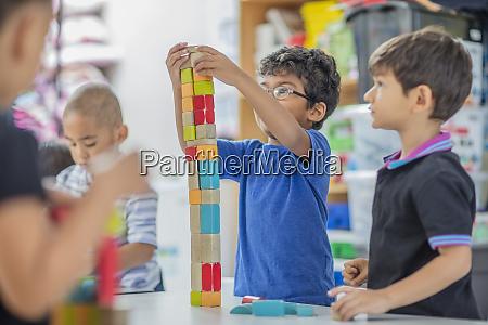 boys stacking building blocks in kindergarten