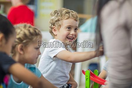 gluecklicher junge mit anderen kindern und