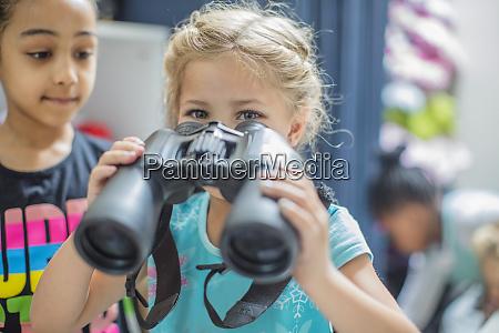 girl holding binoculars in kindergarten