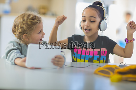 two girls sharing mini tablet in
