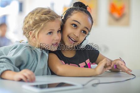 two girls sharing headphones in kindergarten