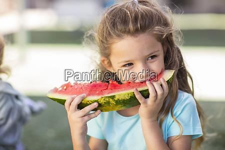 girl eating a watermelon in kindergarten