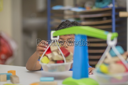 boy playing with toy scales in