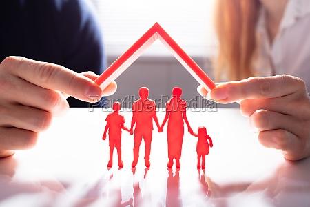 person die familienfiguren mit dach schuetzt