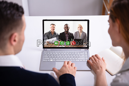 businesspeople video conferencing on laptop