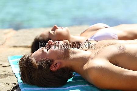 paar sonnenbaden im sommerurlaub am strand