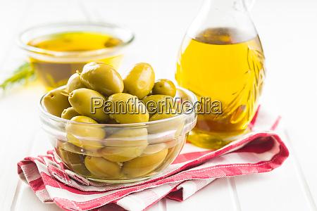 gruene oliven und olivenoel in glasschuessel