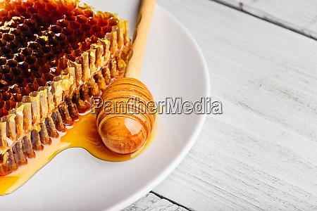 wabe auf teller mit honig dipper