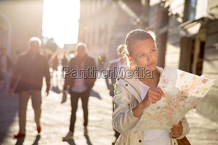 wunderschoene weibliche touristin mit einer karte