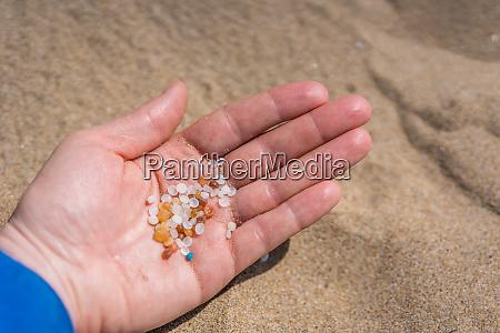 frau haelt winzige schaedliche kunststoff mikroperlen