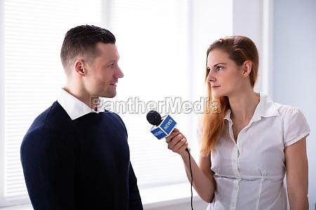 news reporter stellt frage an geschaeftsmann