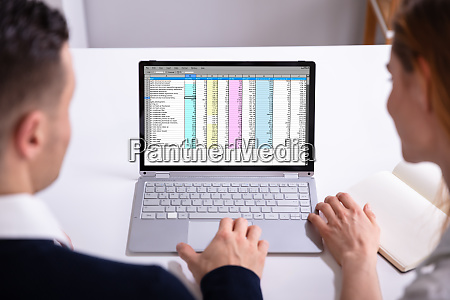 businesspeople checking spreadsheet on laptop screen