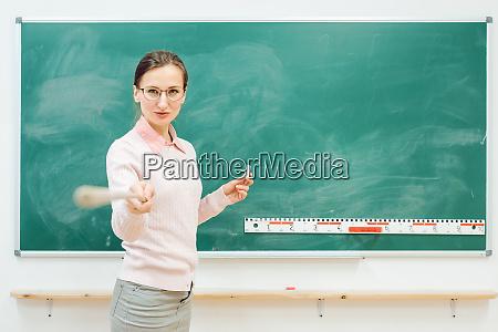 strenger lehrer zeigt mit zeigefinger vor