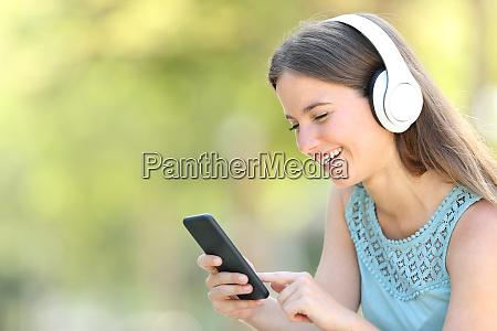 glueckliche frau hoert musik mit smartphone